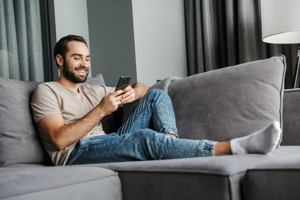 Cheerful man using mobile apps