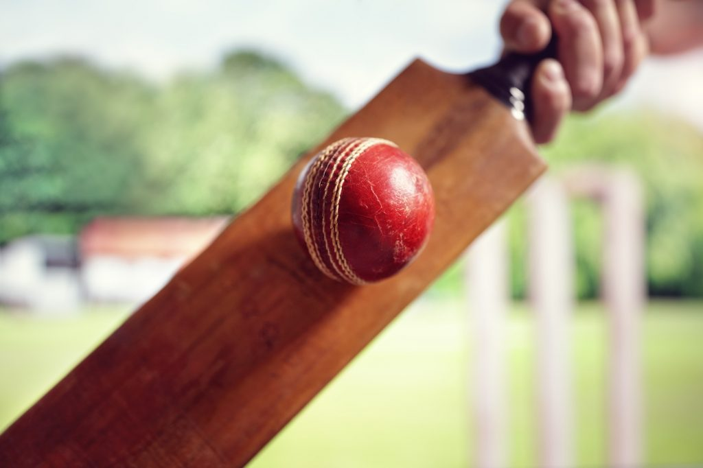Cricket player hitting ball for cricket betting app