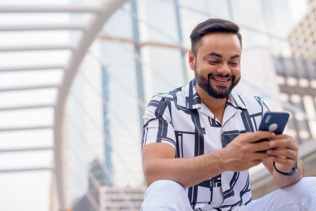 Happy Indian man using phone app
